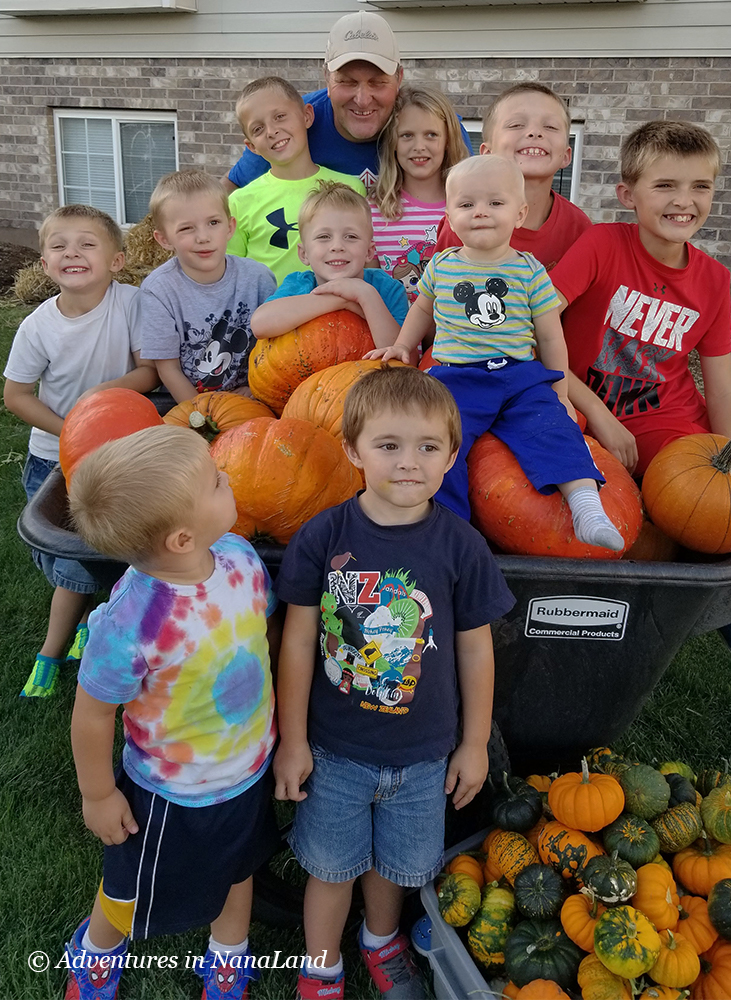 Kids and their grandpa sitting with pile of pumpkins - Gardening with kids - Adventures in NanaLand