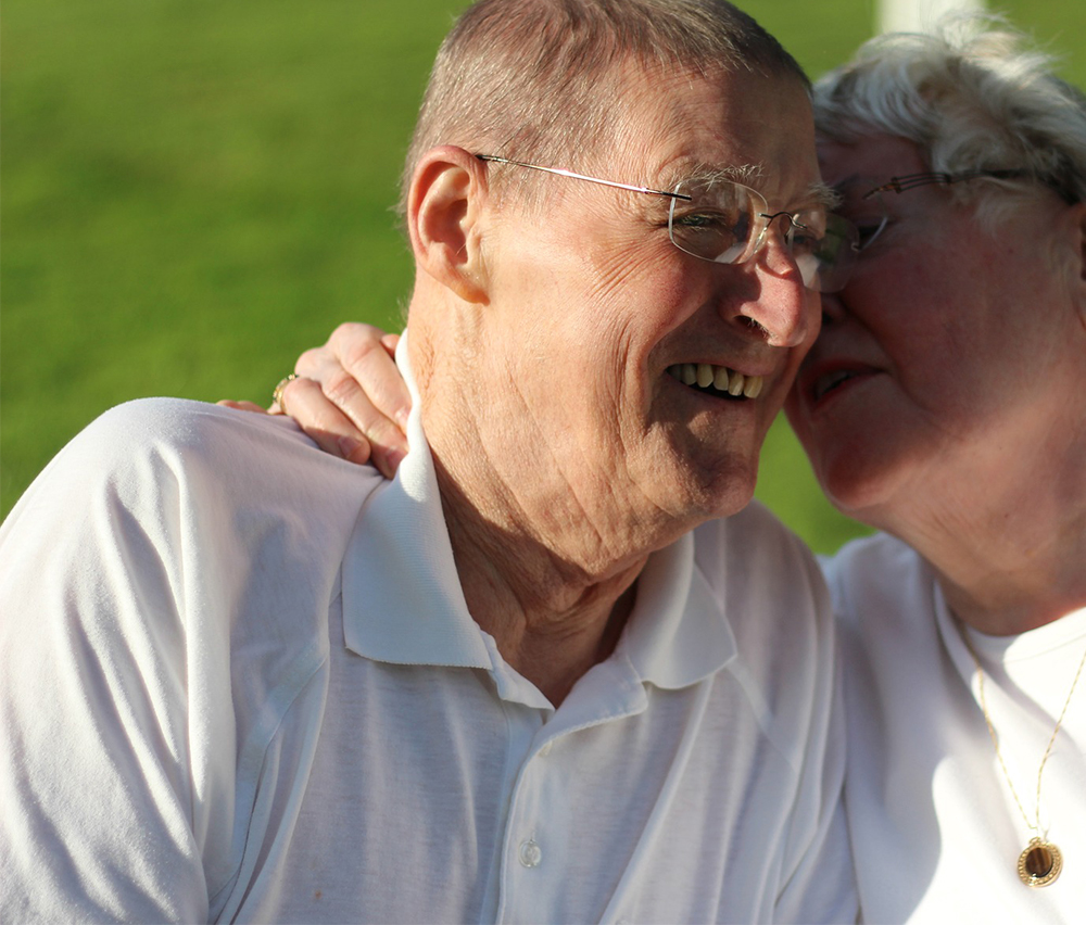 Woman whispering in man's ear square photo - Grandparents Day activities - Adventures in NanaLand