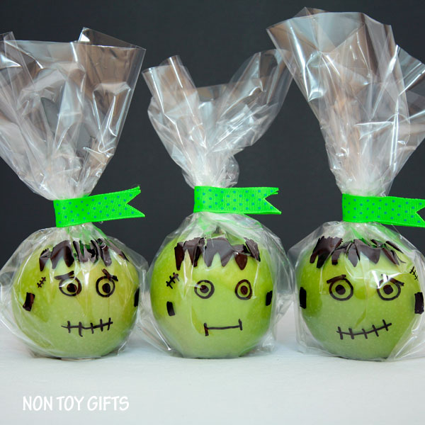 Green apples wrapped in cellophane with Frankenstein faces drawn on the bag in front of the apple - Non Toy Gifts