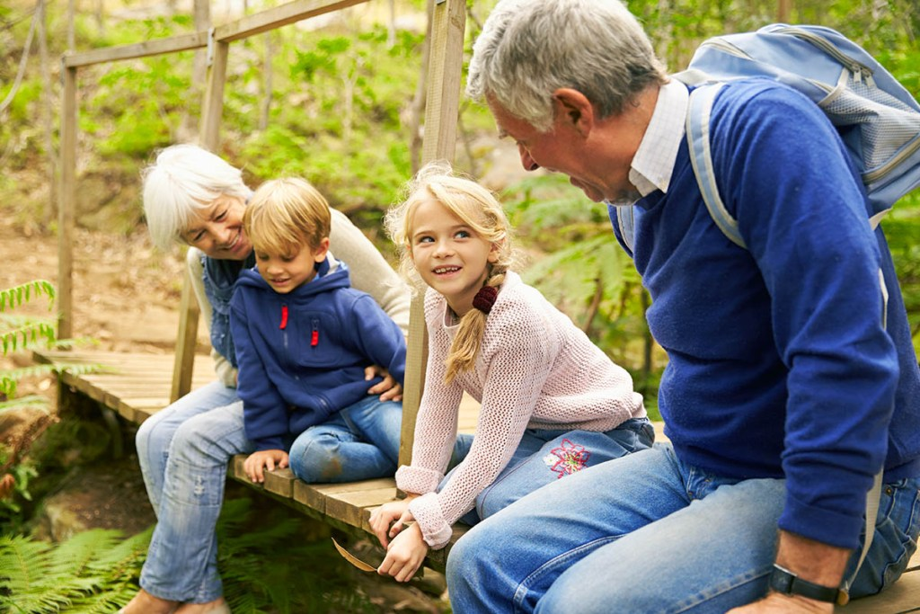 Grandparents sitting with grandkids on wooden bridge - What is Grandma Camp - Adventures in NanaLand