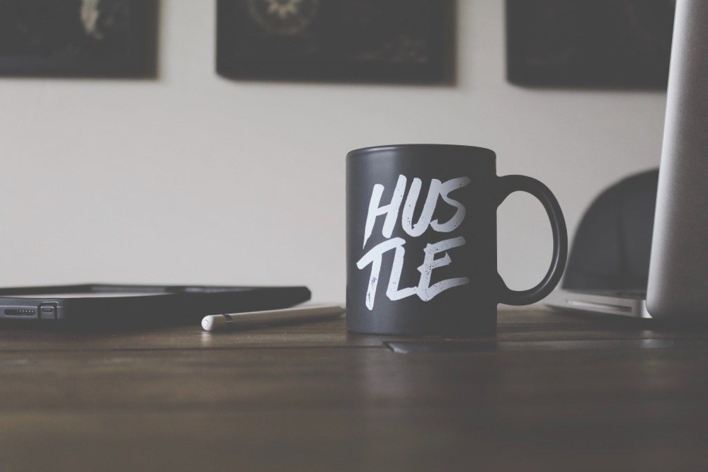 black mug with the word HUSTLE
