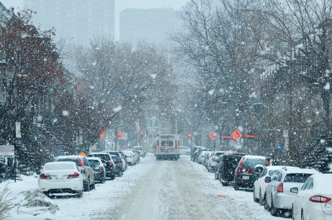 snow falling on busy street with cars