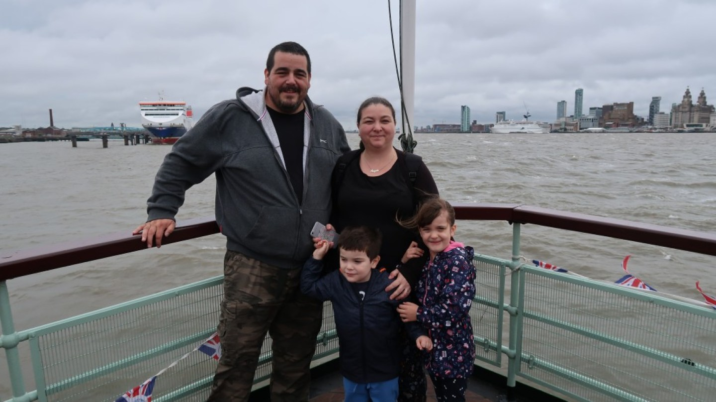 family standing at the prow of mersey ferry snowdrop during crossing