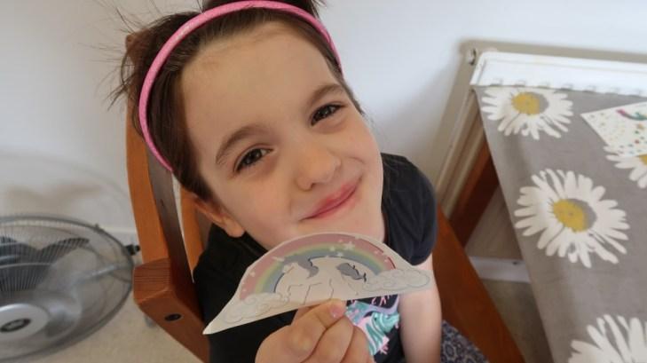 adfc032ba girl wearing pink headband preparing for her rainbow temporary face tattoo