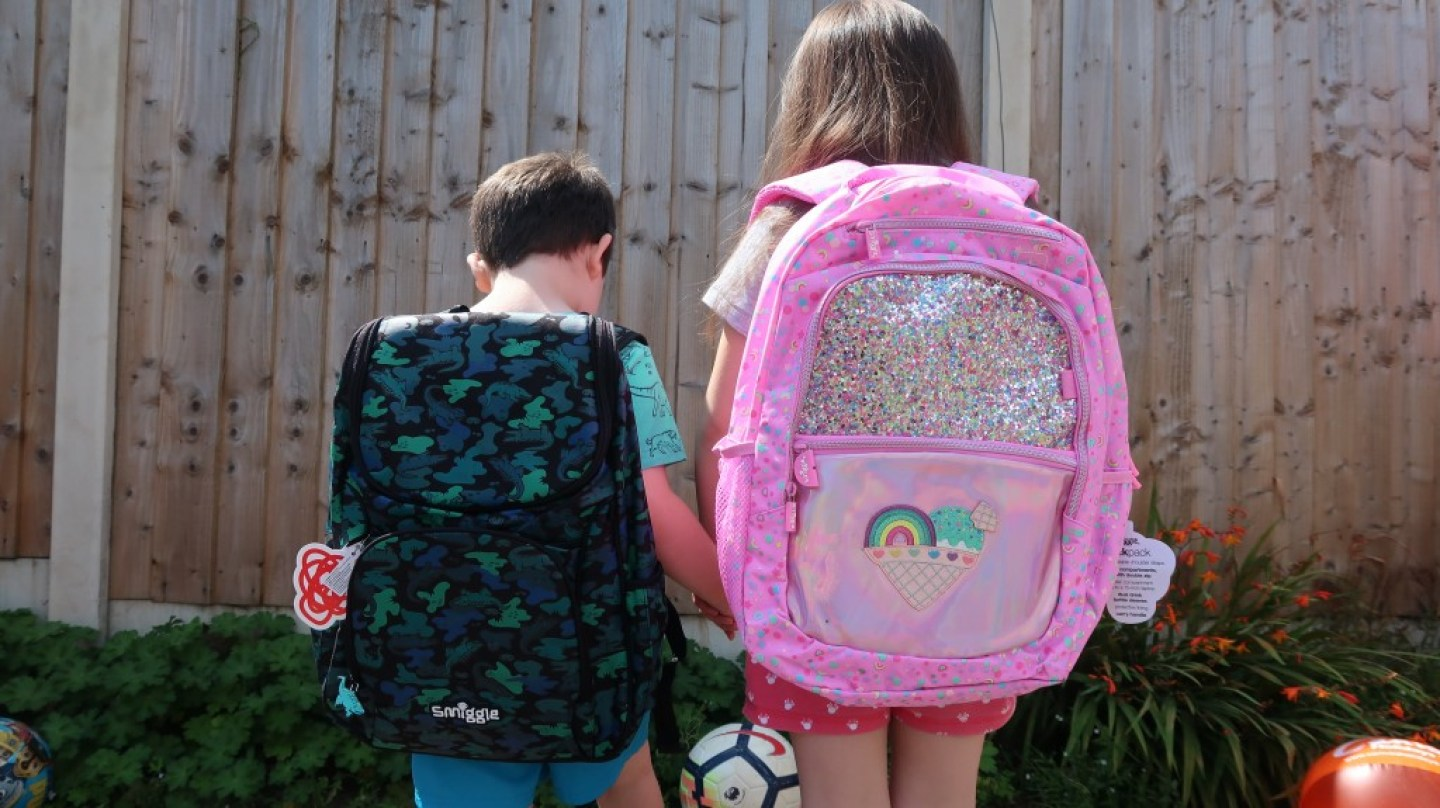 boy and girl wearing their smiggle back packs