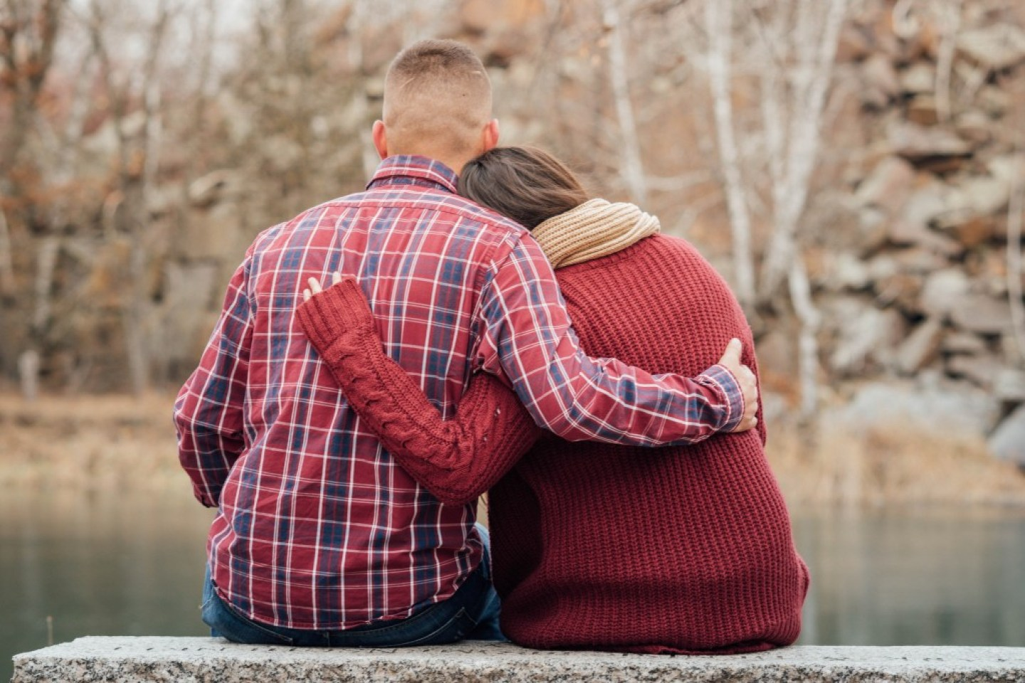 man plaid shirt and woman in jumper  hugging