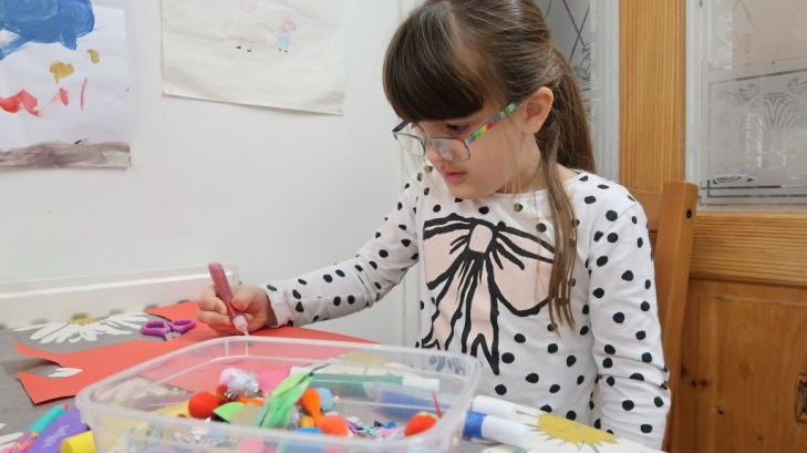 girl in glasses concentratin on a craft project surrounded by materials