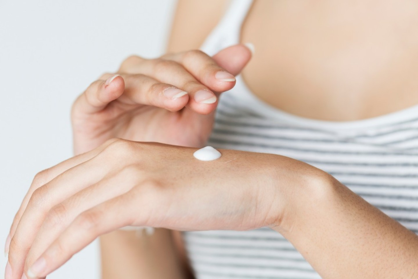 woman with skin cream on hand