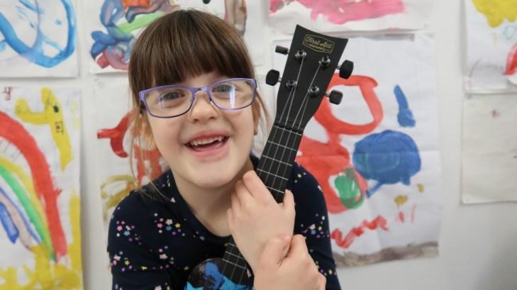 girl with glasses smiling holding ukulele