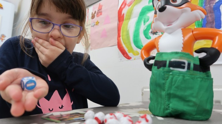 girl in glasses rolling dice playing foxy pants