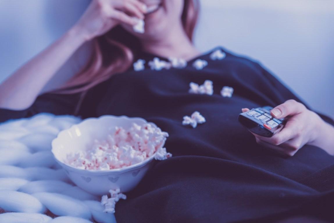 woman eating popcorn watching TV