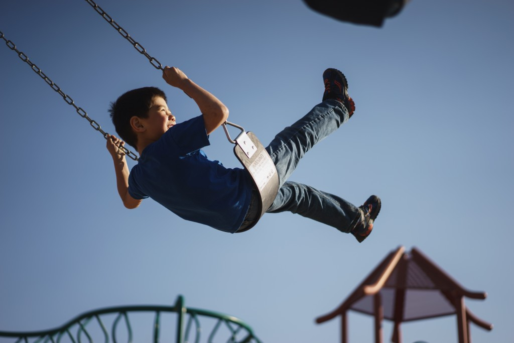 little boy on a swing in the air