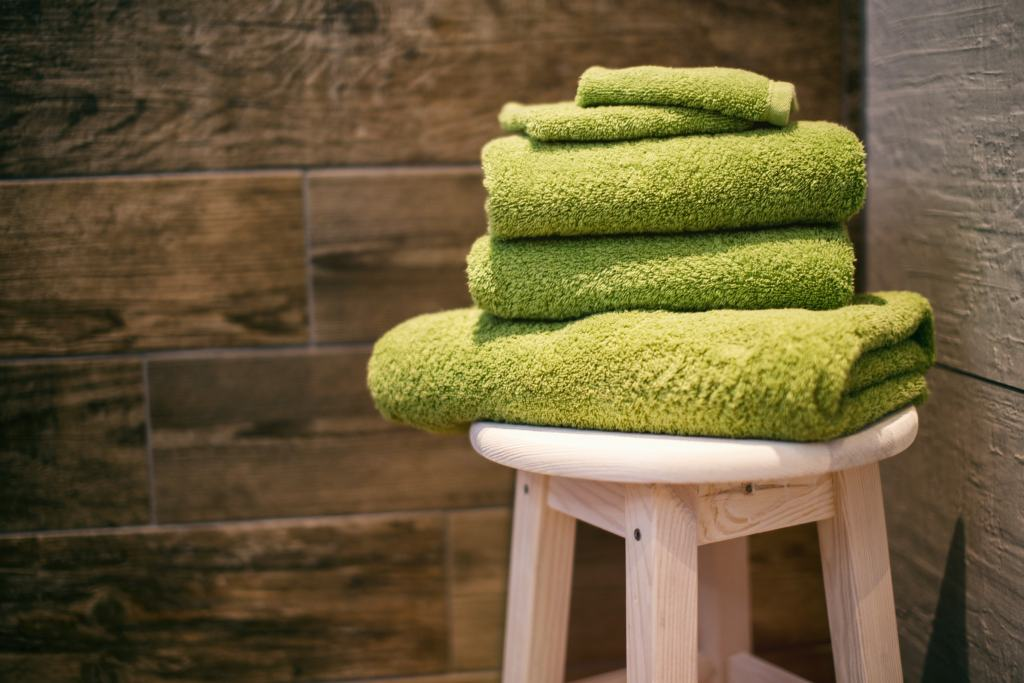 green bathroom towels in a white stool