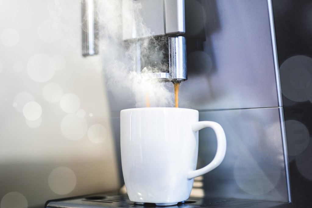 white coffee mug filling with coffee and steam