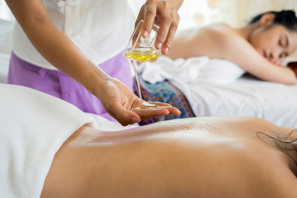 massage oil being poured onto hand and back
