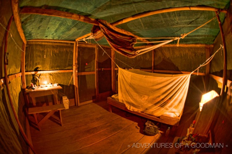 """It doesn't get more """"off the grid"""" than the inside of my hut: a desk, stool, shelf, hard bed and mosquito net."""