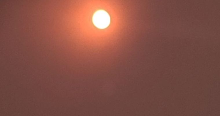 Wildfires giving a red tint to sun, moon