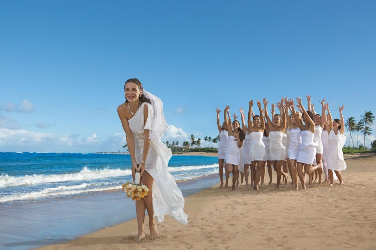 Destination wedding bride throwing bouquet to bridesmaids on the beach at an all inclusive Breathless Resort