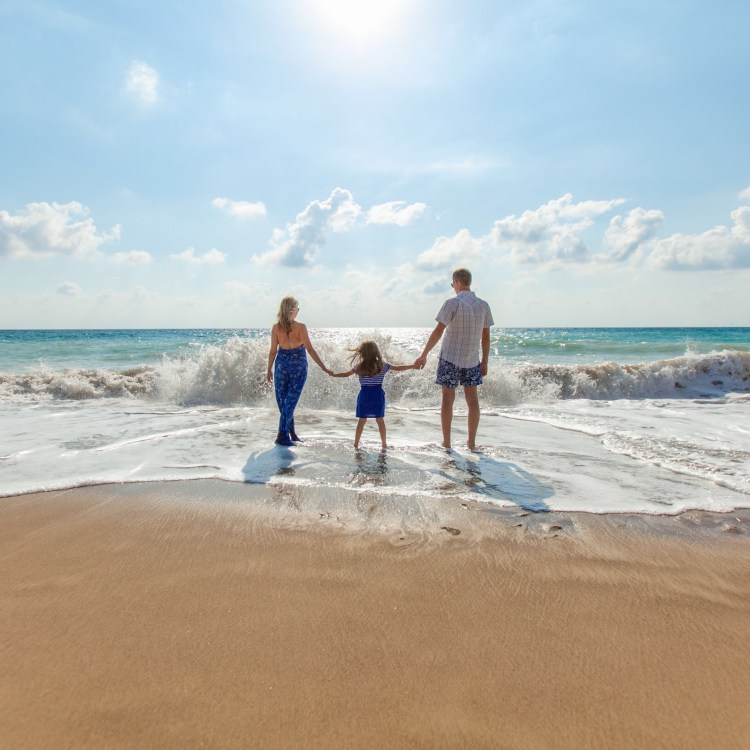 Family vacation with mom, dad, and daughter holding hands in the waves on the beach enjoying a long day of fun