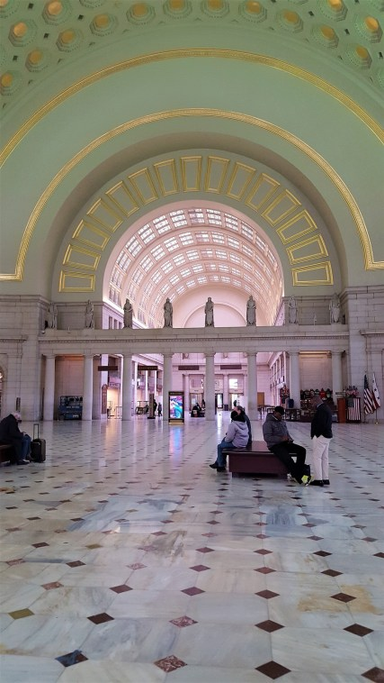 This is a view of the main hall. It originally was an open floor plan, much like what is seen here. During the decades after 1907, the main hall gained ticket counters, a visitor center, and other obstructions that closed off the open floor plan. When restorations began after 2011, getting back to the original open floor plan was a key goal of the work.