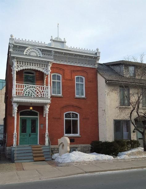 I couldn't find any information about the history of this building. It is a Victorian era home and has some pretty neat Eastlake style elements with the roof line and the second story balcony. The building is currently the home of a art gallery: Jean Claude Bergeron.