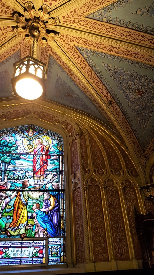 This is a view of one of the stained glass windows seen in the aisle right to the nave (the center aisle of the church). You can also see the details of the ceiling vaults beneath the upper gallery.
