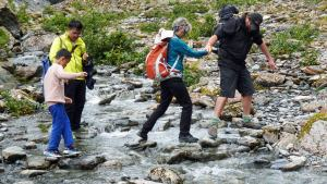 Glacier Valley Eco Tours guide helping tour group across Franz Josef glacier stream
