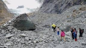 Glacier Valley Eco Tours - Group approaches a large ice boulder from the Franz Josef Glacier