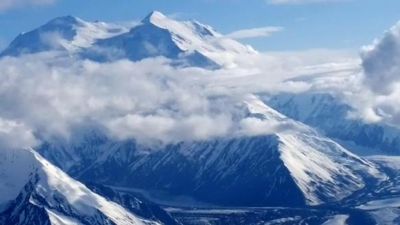 Close-up as Denali appears above the clouds
