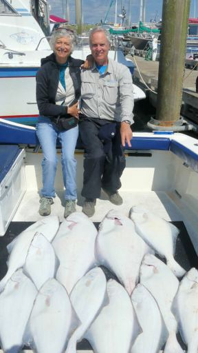 Wendy and Tom pointing to all of the halibut caught