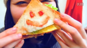A Chinese girl draws a smiley face on a sandwich with ketchup.