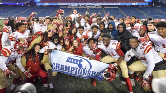 Everett players pose with the MIAA Championship banner after their 35-10 MIAA Div. 1 Super Bowl win over Xaverian at Gillette Stadium, Saturday, Dec. 2, 2017.
