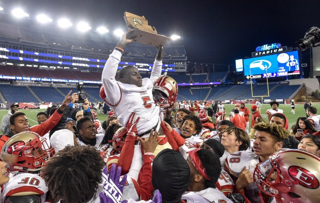 Mike Sainristil of Everett celebrates with the MIAA Div. 1 Super Bowl trophy after defeating Xaverian 35-10 at Gillette Stadium, Saturday, Dec. 2, 2017.