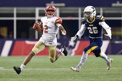Jason Maitre of Everett runs the ball as he is trailed by Cooper DeVeau of Xaverian during their 35-10 MIAA Div. 1 Super Bowl win at Gillette Stadium, Saturday, Dec. 2, 2017.