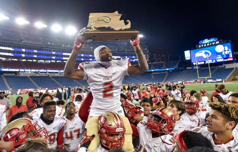 Jason Maitre of Everett celebrates with the MIAA Div. 1 Super Bowl trophy after defeating Xaverian 35-10 at Gillette Stadium, Saturday, Dec. 2, 2017.