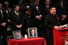 Father Jairo Alfonso recites a payer in memory of late school committee members Robert Carreiro and Richard Baniewicz.