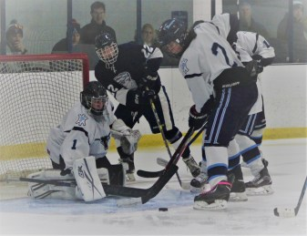 Peabody goalie Lucas DeMild and teammate James Guiry attempt to secure the puck with Lynnfield's Chris Flannery on the doorstep.