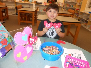 A PAIR OF HEARTS: Anthony Sazo, 6, makes a Valentine's Day heart for himself and one for his late great-grandmother this week at the Saugus Public Library (Saugus Advocate Photo by Mark E. Vogler)
