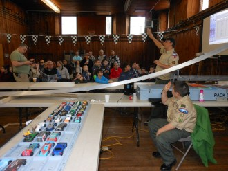 ATTENTION PLEASE: Saugus Pack 62 Cubmaster Bill Ferringo signaled for silence so he could give instructions to cubs participating in last Saturday's Pinewood Derby, which was held in the basement of Cliftondale Congregational Church.
