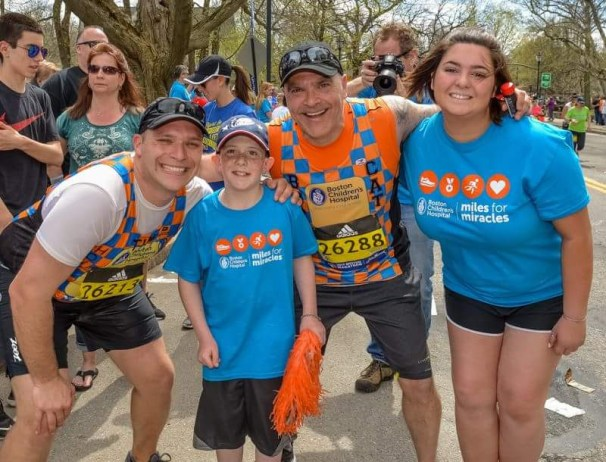 """RUNNING FOR KIDS: Bob Catinazzo, in rear row, wearing orange jersey, says he will be running in Monday's Boston Marathon on behalf of three """"patient partners"""" from Boston Children's Hospital's Miles for Miracles program. This is a photo of Catinazzo during last year's marathon at Mile 13, joined by, left to right, teammate Tim McQuade, Patrick Martinage of Burlington and Tyla Morgante of Saugus. (Courtesy Photo to The Saugus Advocate)"""