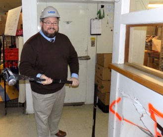 Citizens Inn Executive Director Corey Jackson took a swing at Haven from Hunger's kitchen wall during the April 6 groundbreaking event to renovate the existing cooking area.