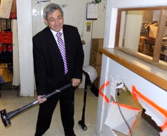 State Rep. Theodore Speliotis took a swing at the kitchen wall during the April 6 groundbreaking event to renovate the kitchen area of Citizens Inn's Haven from Hunger program.