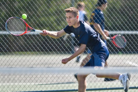 Lynnfield's first singles player Max Rothermund reaches to make the return during their match against Ipswich at Ipswich High School on Monday, May 7, 2018.