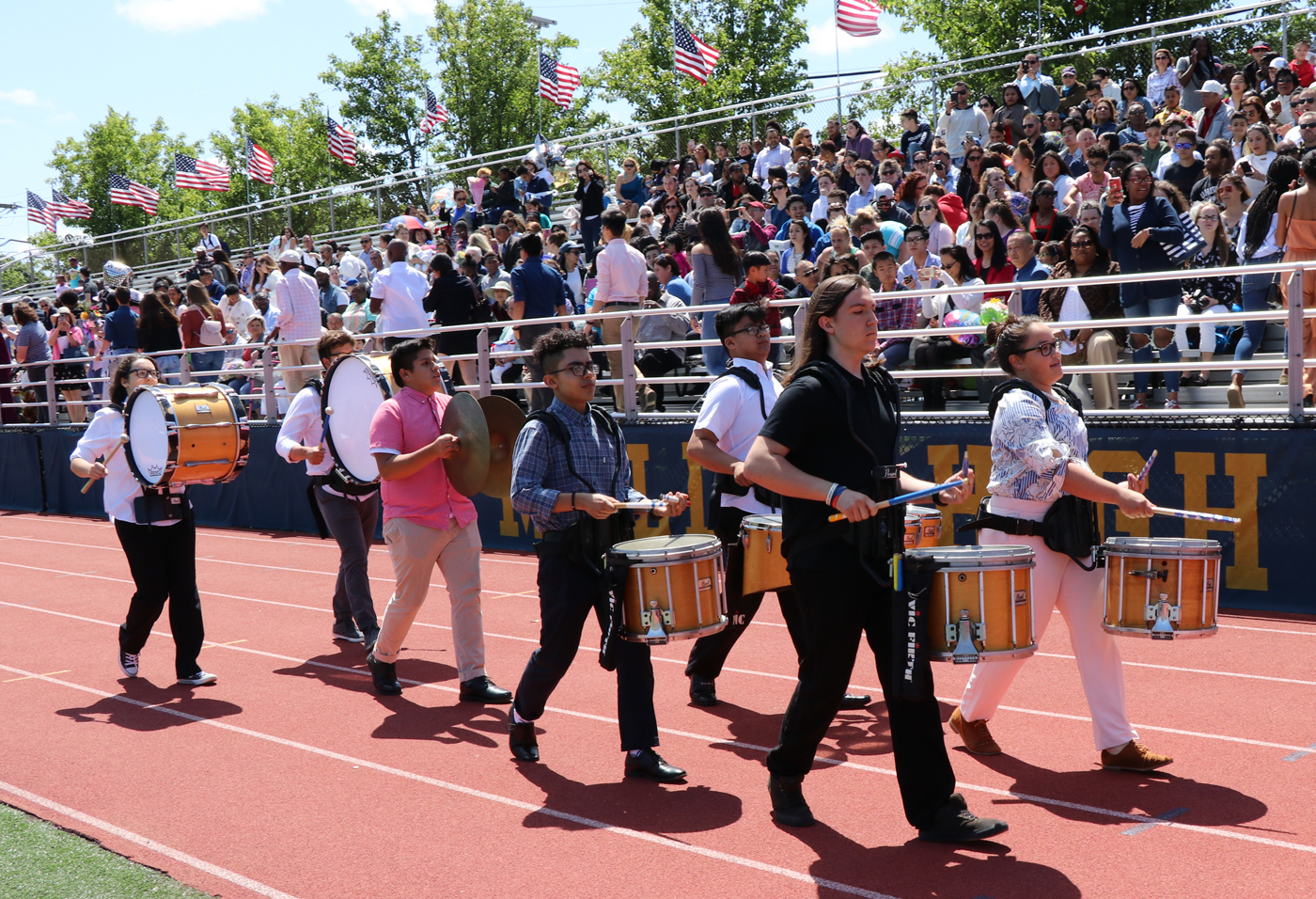 The drummers from the MHS Band lead the procession into the stadium.
