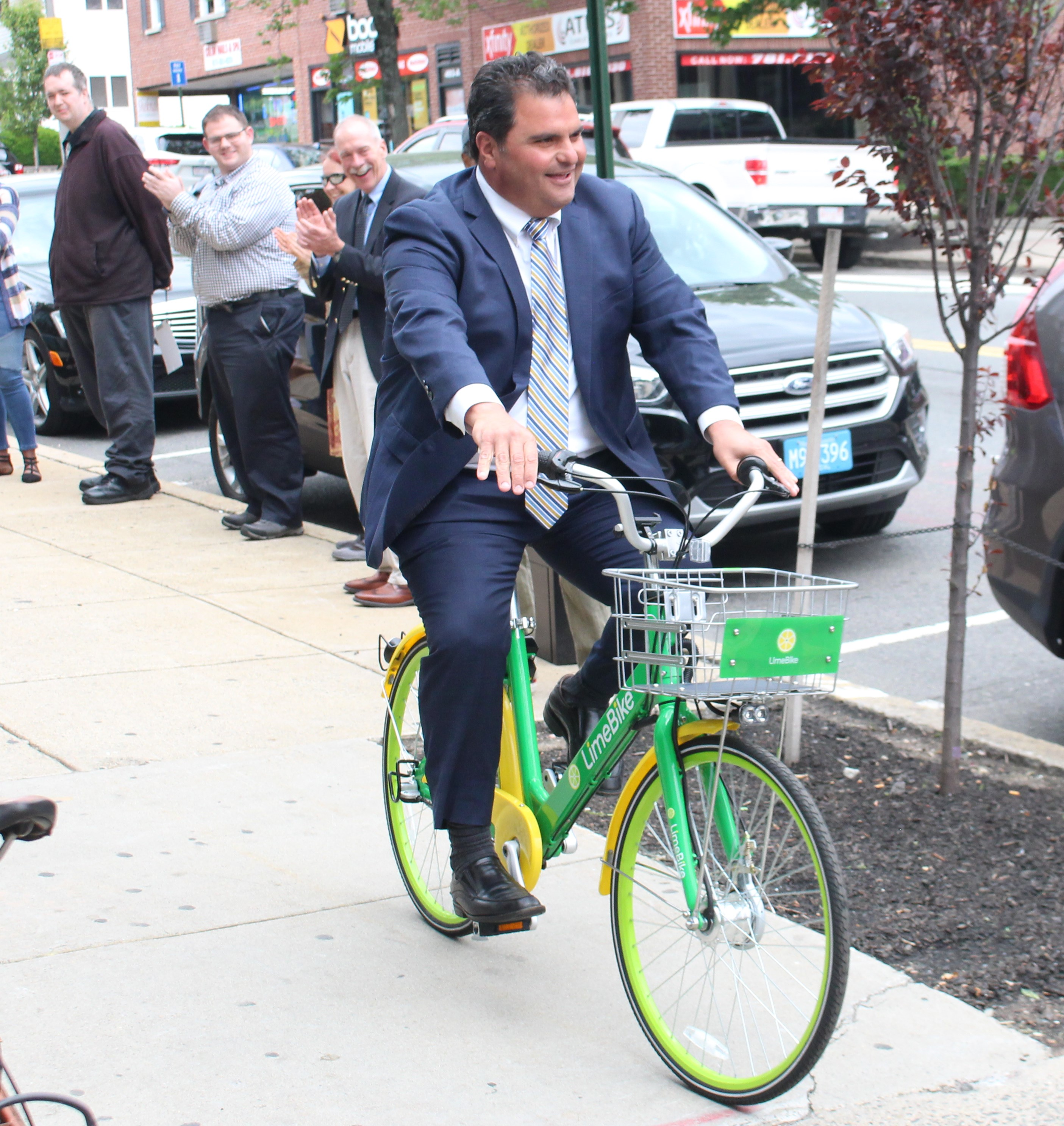 Mayor Carlo DeMaria takes one of the city's new Limebikes for a spin around the block.