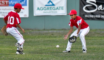 Christian Delgado and Albert Santana of Everett field a ball hit to the outfield during their Little League District 12 game 6-2 loss to Medford at Gillis Park in Medford on Thursday, July 12, 2018.