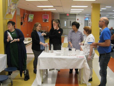 SERVING ICE CREAM--Employees of Malden Public Library are ready to serve ice cream sundaes to youngsters at Malden High School last week.