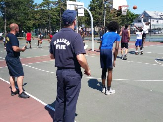 Malden firefighters and police officers volunteered to referee and keep score at the popular Greg Lucey Basketball Tournament at Devir Park.