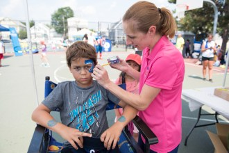 To match his shirt, Christine Z painted a blue shark on Felipe Oliveira's cheek at Devir Park on Tuesday.