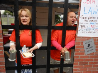 "BEGGING FOR BAIL: Board of Selectmen Chair Debra Panetta and Selectman Jeff Cicolini beseech residents to help them get out of the SAUGUS BAND-ITS JAIL at the 38th annual Founders Day celebration last Saturday. The ""bail money"" helps the Saugus High School Band."